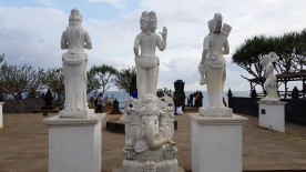 White stone sculptures of Buddhist deities and the Elephant God Ganesh stand on site at the edge of the sea.