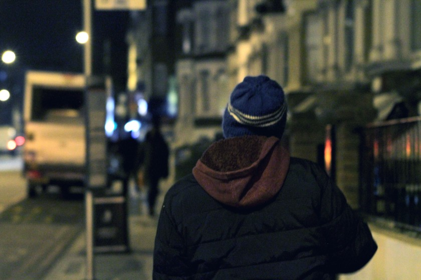Seen from the back, a figure walks along an urban street at night.
