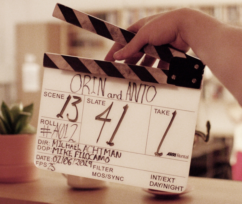 Hand holds a film clapper board with Orin & Anto details